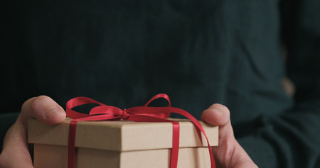 Closeup female hands shows gift box with red ribbon bow, wide photo