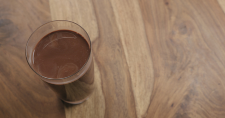 Hot cocoa in glass on wood background with copy space, wide photo Stock Photo