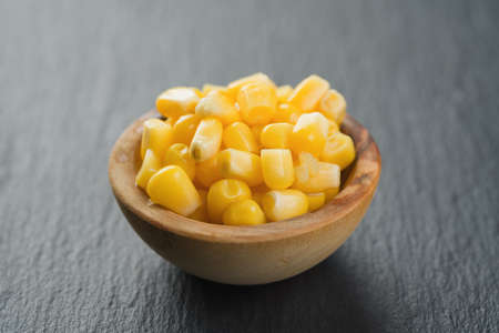 canned corn kernels in wood bowl on slate background