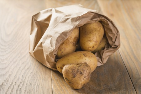 fresh raw potatoes in paper bag on wood background