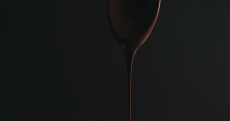closeup melted dark chocolate dripping from spoon over black background 免版税图像