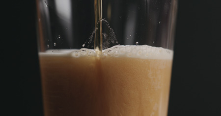 closeup pouring ale beer in a glass over black background