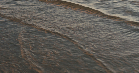 closeup of small waves with caustics on a beach at sunset, wide photo