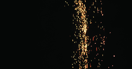 hot sparks slowly falling from above black background