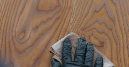 Closeup man applying protective oil finish to ash floor