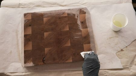 woodworker applying oil finish to walnut end grain wood board from above