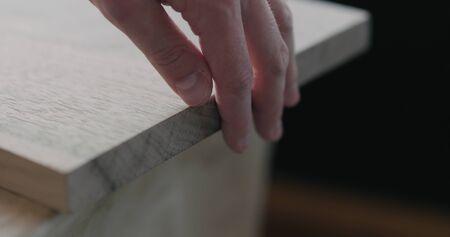 woodworker touching untreated white walnut board