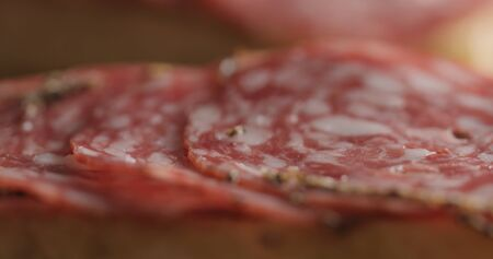 Extreme closeup laying salami slices on ciabatta, wide photo
