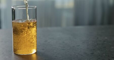 pour pear cider into glass on terrazzo countertop with copy space, wide photo Stock Photo