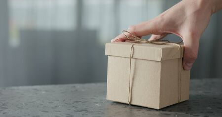 man hand bring brown paper gift box on terrazzo countertop Banque d'images