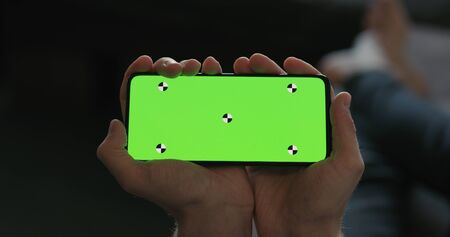 man hold smartphone with green screen while lying on a couch Stock Photo