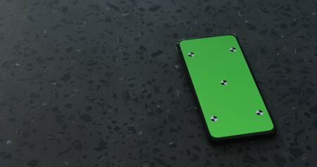 smartphone with green screen on terrazzo surface Stock Photo