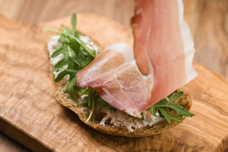 making of italian sandwich with speck and arugula , shallow focus