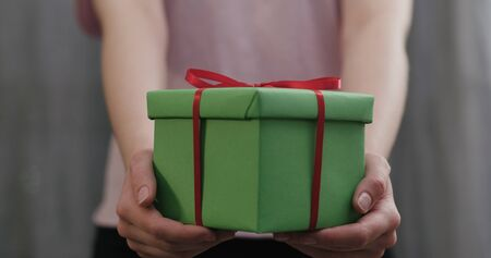 young woman stand and show green gift box with red ribbon bow