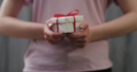 blurred young woman stand and show white gift box with red ribbon bow