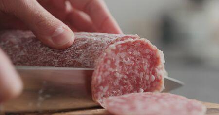 man slicing salame sausage on olive wood board