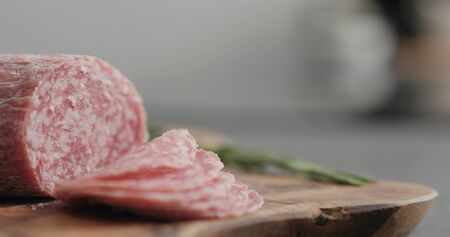 sliced salame sausage on olive wood board