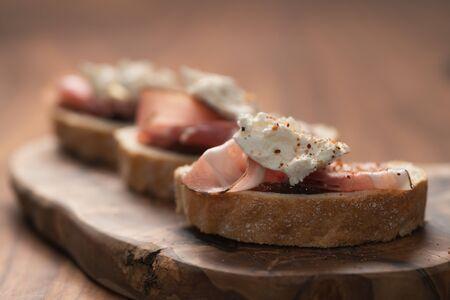 Bruschetta with panchetta, ricotta and fig jam, shallow focus Foto de archivo - 138091712