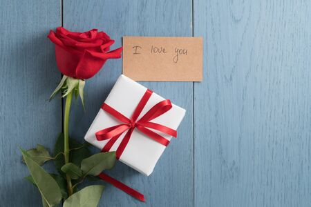 Top view of red rose on blue wood table with i love you paper card and gift