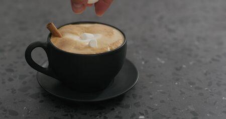 adding marshmallow stick into cappuccino in black cup on terrazzo countertop, wide photo