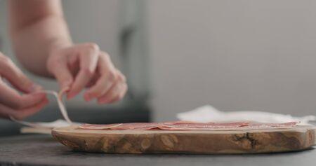 man unpack prosciutto on olive board