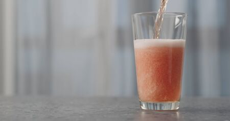 pour orange fizzy drink into pint glass on concrete countertop with copy space