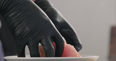 man hands spreading marinade over raw turkey fillet slices in white bowl
