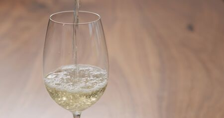 pour white wine in wineglass on table