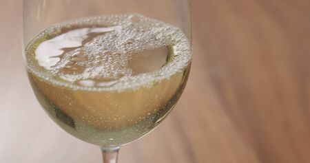 white wine in wineglass on walnut table closeup 写真素材