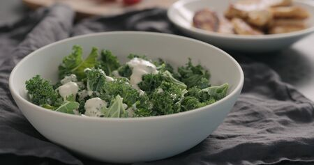 pour caesar dressing on kale leaves in white bowl 写真素材