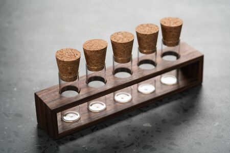 empty walnut holder with glass tubes for spices on concrete surface, shallow focus Archivio Fotografico