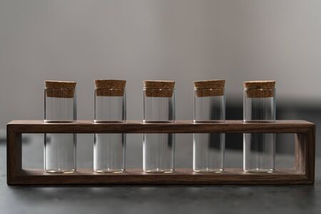 Empty walnut holder with glass tubes for spices on concrete surface Archivio Fotografico