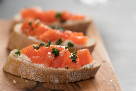 Bruschettas with salmon and cream cheese on olive wood board, shallow focus