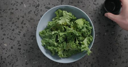 Top view massaged kale leaves in blue ceramic bowl on concrete background, wide photo
