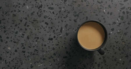 coffee in black cup on concrete background top view