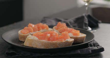 bruschetta with cream cheese and salted trout on black plate Stock Photo