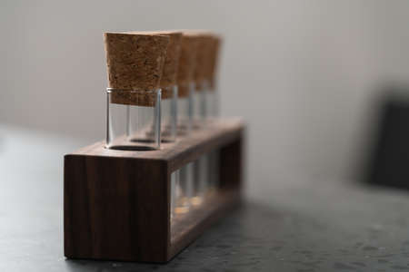 empty walnut holder with glass tubes for spices on concrete surface