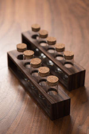 empty walnut holder with glass tubes for spices on walnut table surface