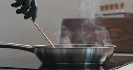 man hand in gloves moving something with wooden spatula in fry pan