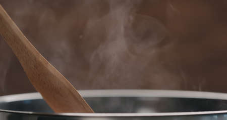 moving something in steel frying pan with wooden spatula