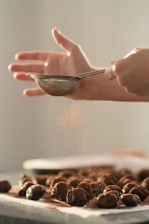 young female hands sprinkle fresh chocolate truffles with cocoa powder on concrete countertop
