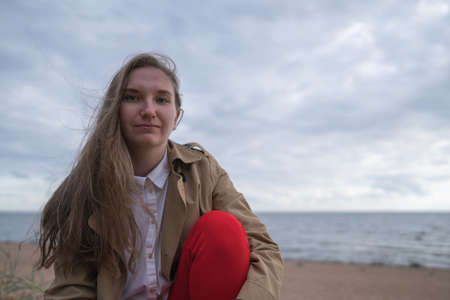 pretty girl sitting on a beach in beige trench coat