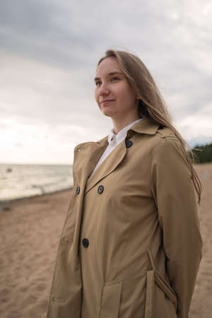 pretty girl walking on a beach in beige trench coat