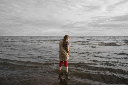 pretty girl walking on a beach in beige trench coat from behind