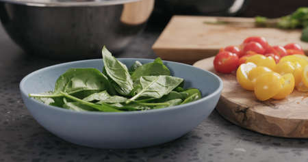 Closeup making salad with spinach, tomatoes and mozzarella in ablue bowl on concrete countertop Stok Fotoğraf