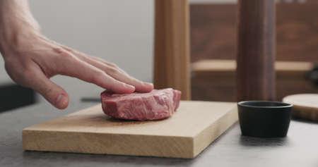 Man hand put raw ribeye steak on oak wood board