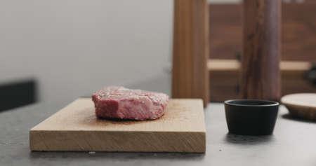 seasoned raw ribeye steak on oak wood board