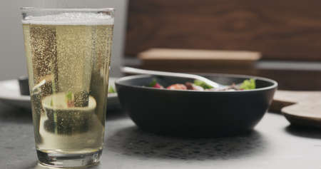 Pour cider into pint glass with salad bowl on a background