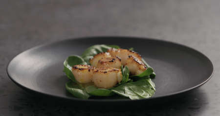 drizzle roasted scallops on spinach with juice from frying in black plate