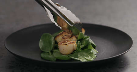 put roasted scallops on spinach in black plate Stok Fotoğraf
